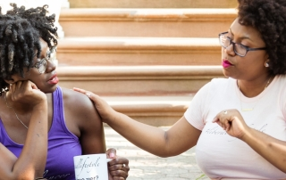 Team members Regina Dowdell and Sydnie Mosley sit on a Brooklyn stoop in the midst of riveting and thoughtful conversation. Regina is wearing a purple tank top and holding a white mug that reads #liberatedlifestyle while Sydnie is wearing a pale pink t-shirt.